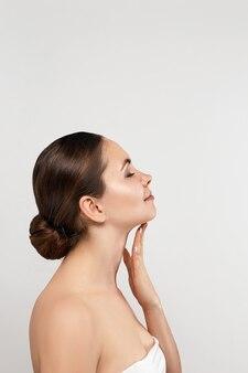 Schoonheid en kuuroordconcept. mooie jonge vrouw met schone frisse huid aanraking gezicht op grijze achtergrond