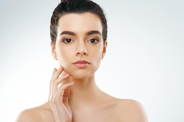 Schoonheid en kuuroordconcept. mooie jonge vrouw met schone frisse huid raakt eigen gezicht aan.