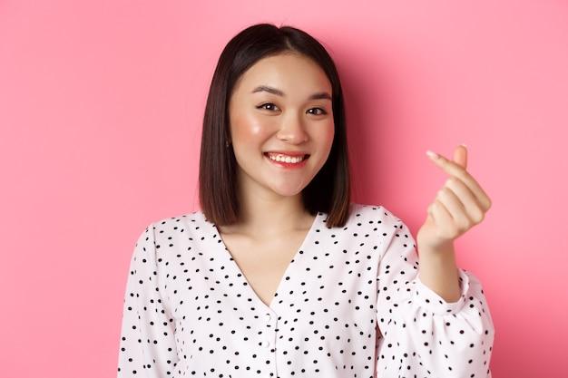 Schoonheid en lifestyle concept. close-up van een mooie aziatische vrouw die een hartteken toont, glimlacht en romantisch voelt op valentijnsdag, staande over een roze achtergrond.