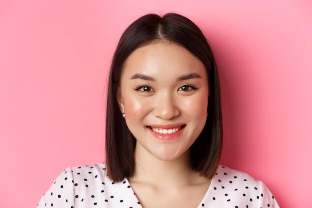 Schoonheid en lifestyle concept. headshot van een mooie aziatische vrouw die lacht, vrolijk en romantisch naar de camera kijkt, staande tegen een roze achtergrond