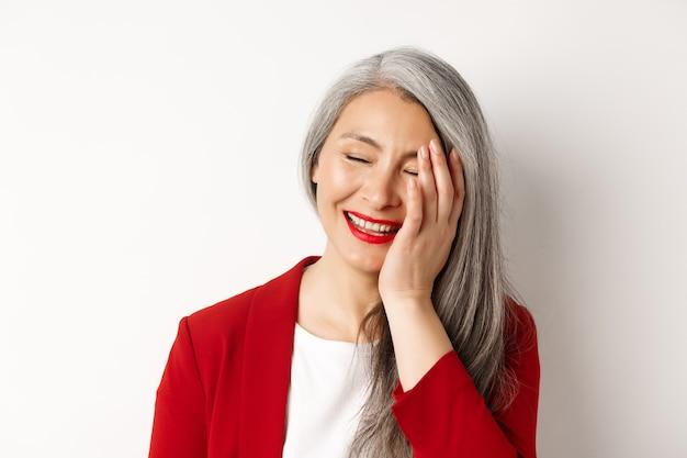 Schoonheid en make-up concept. close-up van mooie aziatische volwassen vrouw, lachend en ontroerend gezicht, glimlachend gelukkig, staande op witte achtergrond.