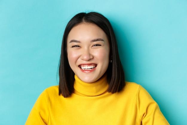 Schoonheid en make-up concept. close up van zorgeloos tienermeisje glimlachend en oprecht lachen, plezier hebben, staande over blauwe achtergrond