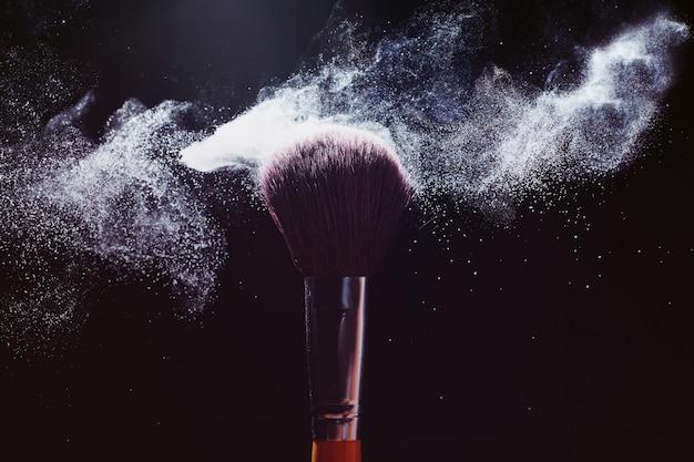 Schoonheid en make-up concept. de schoonheidsmiddelen borstelen het vrijgeven van een wolk van roze fonkelend gezichtspoeder over zwarte achtergrond.