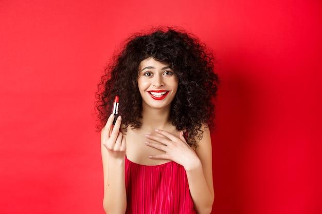 Schoonheid en make-up concept. mooi vrouwelijk model met krullend haar, avondjurk dragen, rode lippenstift tonen en glimlachen, staande op een witte achtergrond.