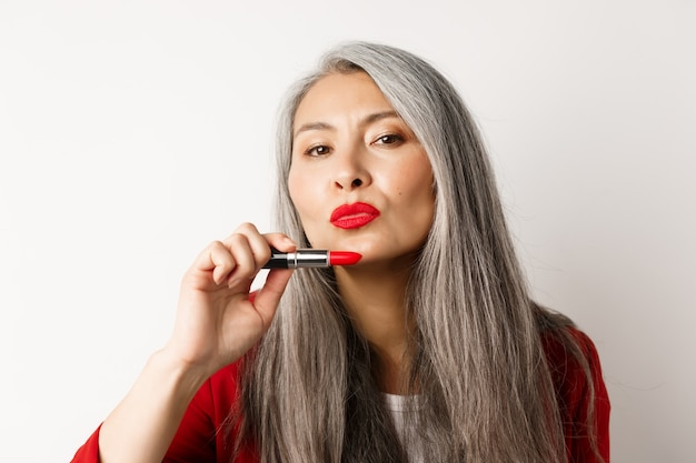 Schoonheid en make-up concept. mooie aziatische oudere vrouw tuit lippen, rode lippenstift tonen en brutaal kijken naar camera, witte achtergrond.