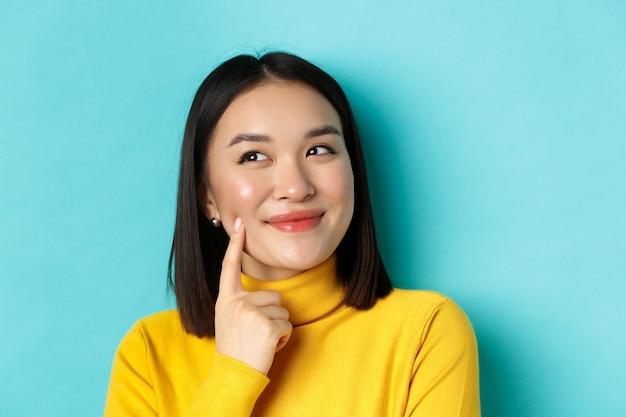 Schoonheid en make-up concept. sluit omhoog van peinzend aziatisch meisje dat, iets voorstelt en naar de linkerbovenhoek kijkt, een idee werpt, zich over blauwe achtergrond bevindt.