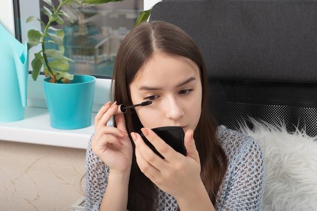 Schoonheid en make-up. meisje schildert ogen met mascara met een borstel, krullen en wimpers scheiden