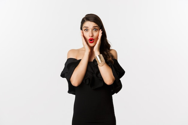 Schoonheid en mode-concept. aantrekkelijke vrouw in glamour zwarte jurk, sieraden en make-up, op zoek verrast en opgewonden, staande op witte achtergrond.