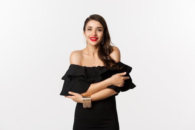 Schoonheid en mode-concept. elegante en mooie vrouw in zwarte jurk, make-up, knuffelen zichzelf en kijken naar camera met sensuele blik, staande op witte achtergrond.