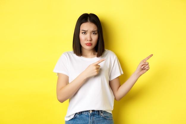 Schoonheid en mode concept. mooie aziatische vrouw in wit t-shirt die met de vingers naar rechts wijst, laat zien dat logo over gele achtergrond staat