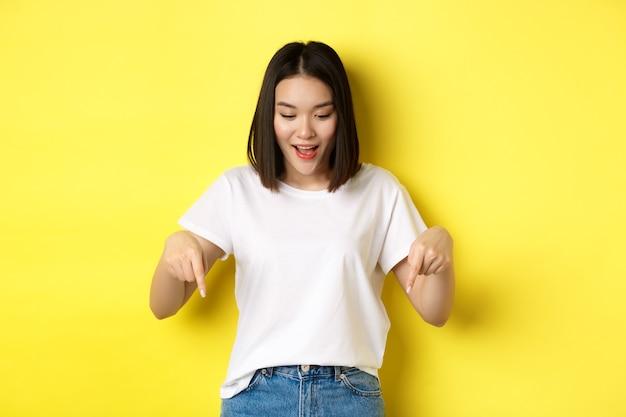 Schoonheid en mode-concept. mooie aziatische vrouw in wit t-shirt wijzende vingers naar beneden, toont logo staande op gele achtergrond. Premium Foto