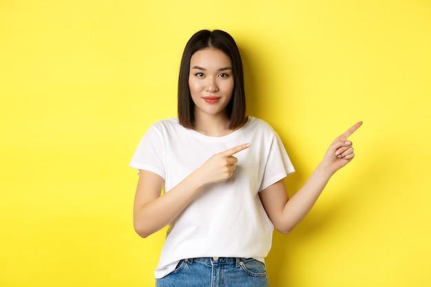 Schoonheid en mode concept. mooie aziatische vrouw in wit t-shirt wijzende vingers naar rechts, demonstreren logo staande over gele achtergrond.