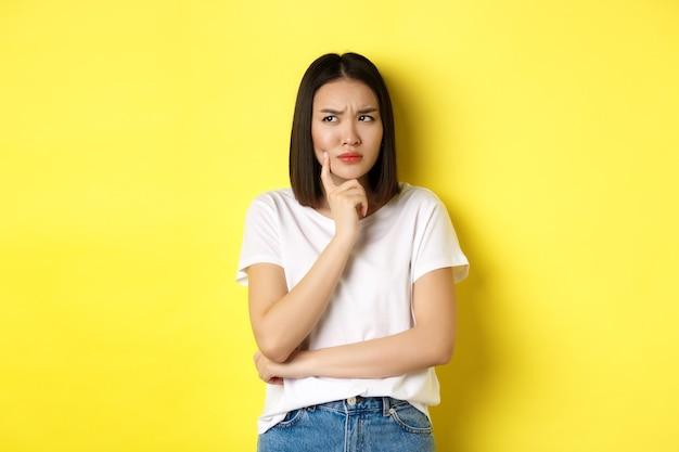 Schoonheid en mode concept. peinzende aziatische vrouw die denkt, bedachtzaam kijkt terwijl ze iets nadenkt, staande over een gele achtergrond.