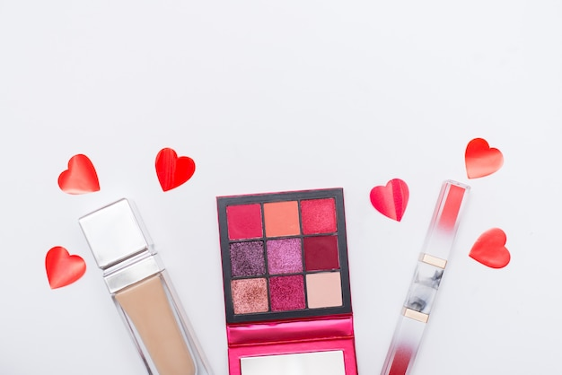 Schoonheid en mode concept. plat leggen van cosmetische en rode harten geïsoleerd