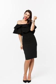 Schoonheid en mode-concept. volledige lengte shot van gelukkige jonge vrouw in luxe zwarte jurk, sieraden en hakken, make-up dragen en tevreden kijken, overwinning vieren, winnende, witte achtergrond.