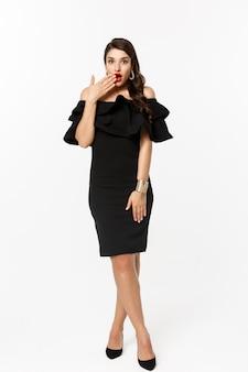 Schoonheid en mode-concept. volledige lengte shot van mooie en koket vrouw in zwarte jurk, open mond en kijken afgevraagd camera, staande op witte achtergrond.