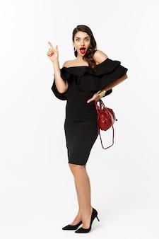 Schoonheid en mode concept. volledige lengte van opgewonden jonge vrouw in glamourjurk, rode lippen, met een idee, vinger opsteken om iets te suggereren, witte achtergrond