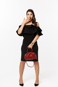 Schoonheid en mode-concept. volledige lengte van verbaasde jonge vrouw in zwarte jurk en hakken met tas, camera kijken verbaasd, deksel geopende mond, witte achtergrond.