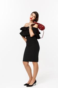 Schoonheid en mode-concept. volledige lengte van vermoeide jonge vrouw op hoge hakken en elegante jurk, portemonnee op schouder houden en kijken met vermoeidheid camera, witte achtergrond.