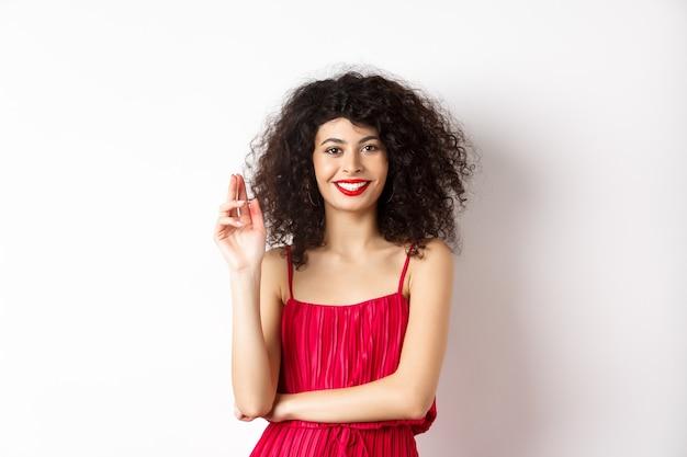 Schoonheid en mode. lachende vrouw met krullend haar en make-up, gekleed in een rode jurk, zwaaiende hand in groetgebaar, hallo zeggen, staande op een witte achtergrond.