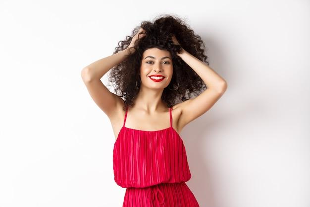 Schoonheid en mode. zorgeloze vrouw in rode jurk en make-up, krullend haar aanraken en gelukkig glimlachen, staande op een witte achtergrond.
