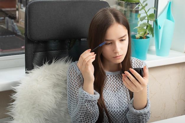 Schoonheid en verzorging. een jong meisje kamt en deelt haar wimpers met een speciaal borsteltje
