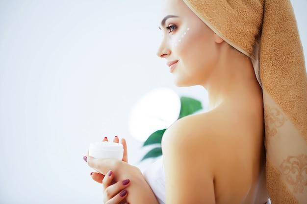 Schoonheid en verzorging, vrouw met pure huid en handdoek op het hoofd giet
