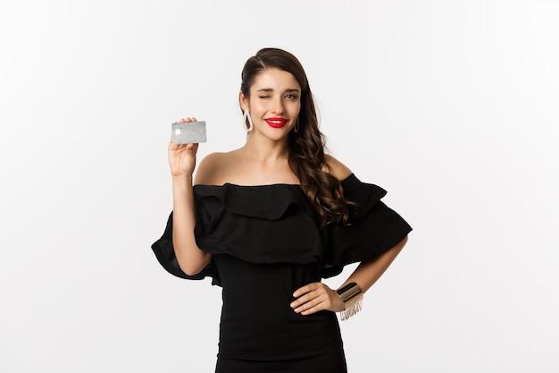 Schoonheid en winkelconcept. modieuze vrouw in zwarte kleding, die make-up draagt, knipoogt naar de camera en creditcard toont, die zich over witte achtergrond bevindt.