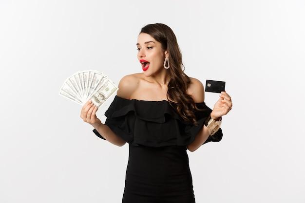 Schoonheid en winkelconcept. modieuze vrouw met creditcard, kijkend naar geld met verbazing, staande op een witte achtergrond.