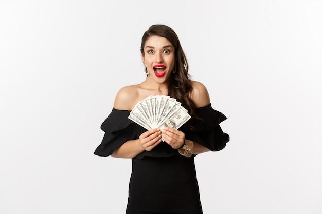 Schoonheid en winkelconcept. opgewonden vrouw in zwarte jurk, geldprijs tonen en gelukkig staren camera, staande op witte achtergrond.