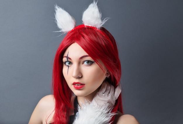 Schoonheid fashion model girl met rode pruik op grijze achtergrond. cosplay-personage uit het spel