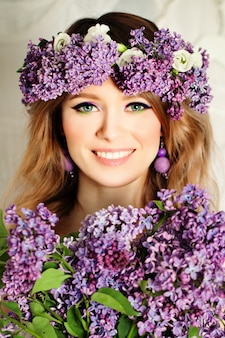 Schoonheid fashion model meisje met lila bloemen kapsel. mooie vrouw en bloeiende bloemen. natuur kapsel. vakantie creatieve violette kleuren make-up en accessoires