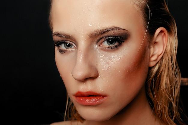 Schoonheid fashion model meisje natuurlijke make-up natte haren op zwarte gouden achtergrond in warme tinten. portret van een jonge vrouw met mode make-up