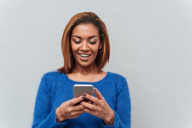 Schoonheid gelukkige afrikaanse vrouw in trui telefoon kijken en bericht schrijven. geïsoleerde grijze achtergrond