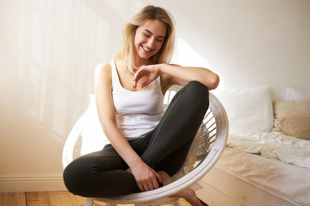 Schoonheid, gezelligheid en ontspanning concept. binnen schot van positieve charmante blanke tienermeisje met losse blonde haren en blote voeten zitten in de slaapkamer in een stijlvolle fauteuil, gelukkig lachend