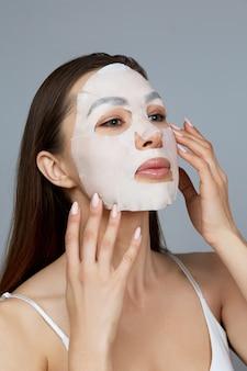 Schoonheid gezicht huidverzorging. de vrouw brengt een vochtinbrengend masker op het gezicht aan. meisjesmodel met kosmetisch masker. gezichtsbehandeling