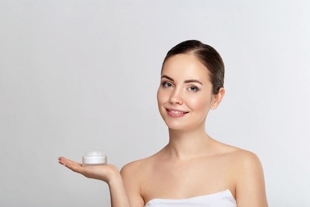 Schoonheid gezicht huidverzorging. mooie vrouw met gezonde gladde gezichts schone huid fles cosmetische crème te houden. model met schoonheidsgezicht. moisturizer gezichtsbehandeling. cosmetologie. spa.