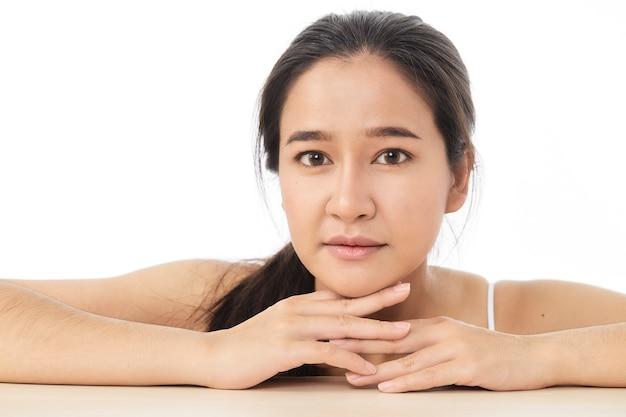Schoonheid gezicht huidverzorging vrouw zittend portret van mooi aantrekkelijk thais aziatisch vrouwelijk model geïsoleerd op wit oppervlak.