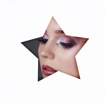 Schoonheid gezicht rode make-up ogen van een jong meisje in een spleet ster gat van witboek