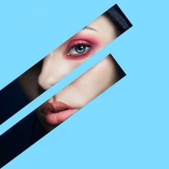 Schoonheid gezicht rode make-up ogen van een jonge vrouw in een spleet gat van blauw papier. vrouw met mooie make-up rode gloeiende schaduw, grote blauwe ogen in het spleetgat