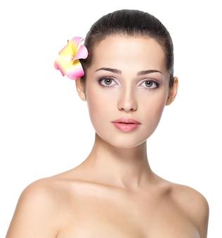 Schoonheid gezicht van jonge vrouw met bloem.