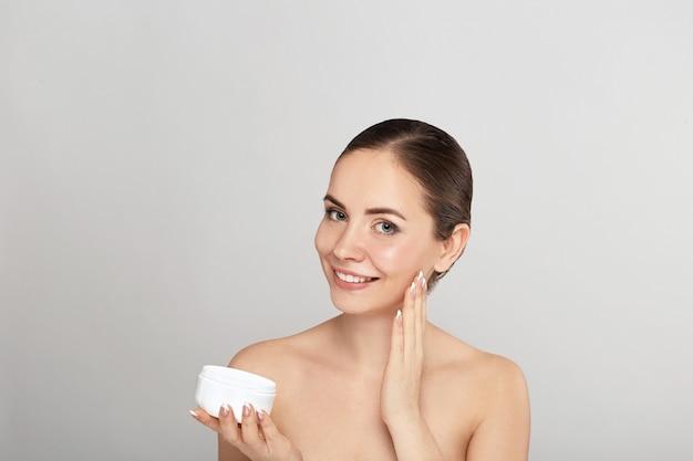 Schoonheid gezicht van vrouw concept. huidsverzorging. portret van vrouwelijk model die kosmetische bevochtigende room houden en toepassen en eigen gezicht aanraken. bescherming van de huid. cosmetologie. spa