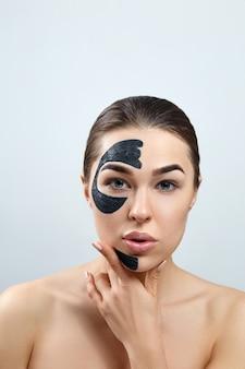 Schoonheid gezichtsmasker. huidverzorging gezicht spa-behandeling. mooie jonge vrouw met zwart masker van klei op gezicht. moisturizer-masker.
