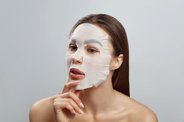 Schoonheid gezichtsmasker. mooie vrouw met een doek hydraterende masker op gezicht. huidverzorging. meisje schoonheid model raakt haar gezicht. spa masker.