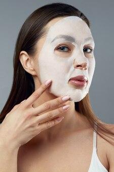 Schoonheid gezichtsmasker. mooie vrouw met een doek vochtinbrengend masker op gezicht. huidverzorging. cosmetisch kuuroordmasker. gezichtsbehandeling