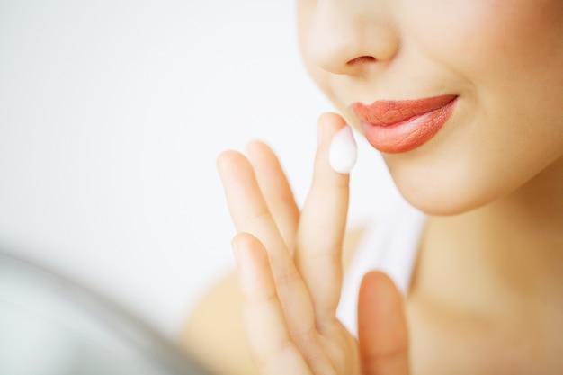 Schoonheid gezichtsverzorging. vrouw die room op huid toepast.