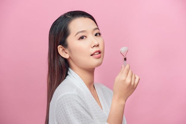 Schoonheid gezichtsverzorging. vrouw doet gezichtsmassage met jade gezichtsrollers voor spa-huidverzorging