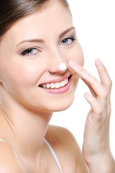 Schoonheid glimlachend vrouwelijk gezicht met druppel cosmetische crème op haar neus