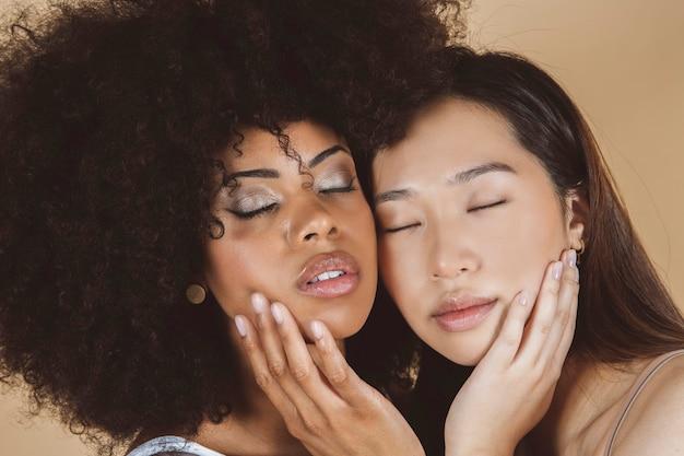 Schoonheid. glimlachende vrouwen met perfecte huid en natuurlijk make-upportret. mooie vrolijke aziatische en afrikaanse meisjesmodellen met verschillende huidtypes in beige. spa huidverzorgingsconcept
