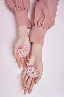 Schoonheid handen vrouw met roze bloemen in haar handen op tafel. natuurlijke cosmetica voor handverzorging
